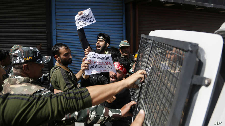 Indian policemen detain Kashmiri Shiite Muslims as they shout pro-freedom slogans after they made an attempt to take out a religious procession during restrictions in Srinagar, Indian controlled Kashmir, Sunday, Sept. 8, 2019. Authorities in Indian…