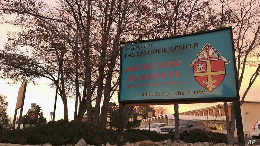 FILE - In this Nov. 29, 2018, file photo, the sun sets on a sign in front of the Archdiocese of Santa Fe offices in Albuquerque, N.M. A former Roman Catholic priest found guilty of sexual abuse in New Mexico is scheduled to be sentenced Friday, Sept…