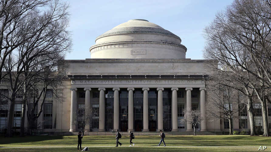 """FILE - In this April 3, 2017 file photo, students walk past the """"Great Dome"""" atop Building 10 on the Massachusetts Institute of Technology campus in Cambridge, Mass. Two prominent researchers are quitting MIT's Media Lab over revelations that the…"""