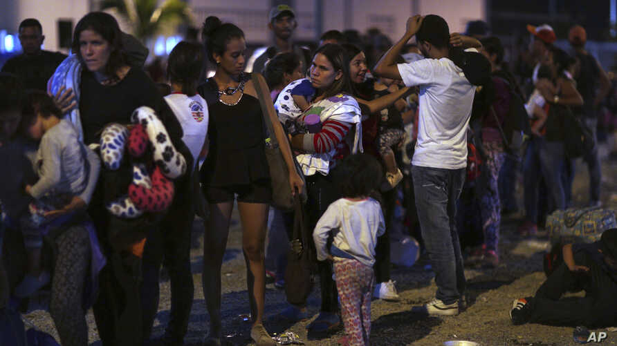 Venezuelans wait to pass immigration control at the Ecuador-Peru border, before the deadline on stricter regulations that require passports, in Tumbes, Peru, Friday, June 14, 2019.