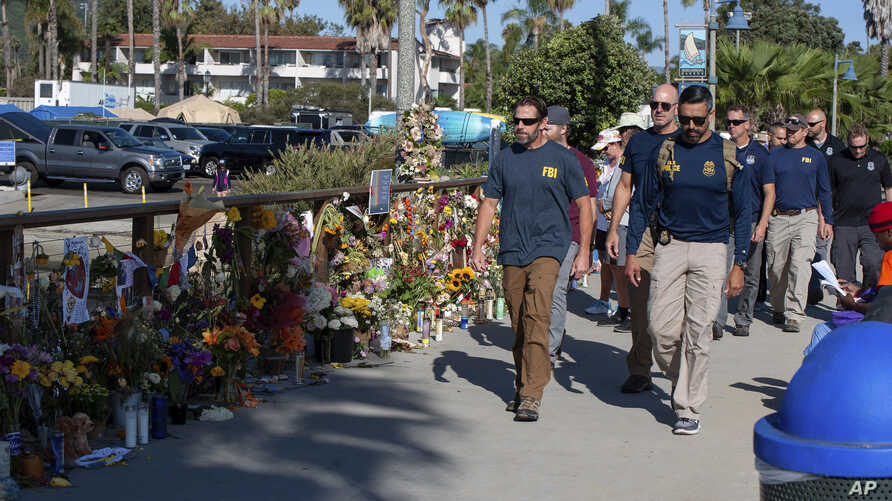 FBI agents walk past a memorial for the victims of the Conception dive boat on the Santa Barbara Harbor, as authorities issue a search warrant for the Truth Aquatics' offices in Santa Barbara, Calif., Sunday, Sept. 8, 2019. The office was ringed in…