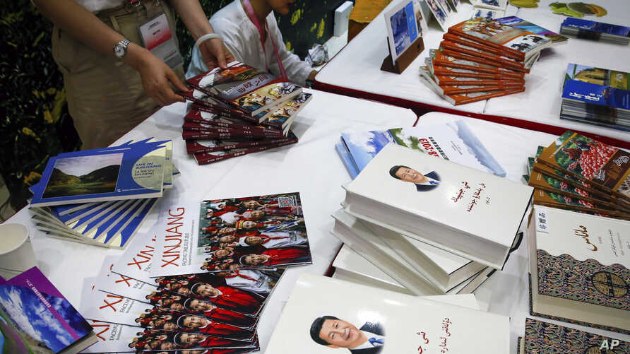 Copies of the book on the governance of Chinese President Xi Jinping are displayed with booklets promoting Xinjiang during a press conference by Shohrat Zakir, chairman of China's Xinjiang Uighur Autonomous Region, at the State Council Information…