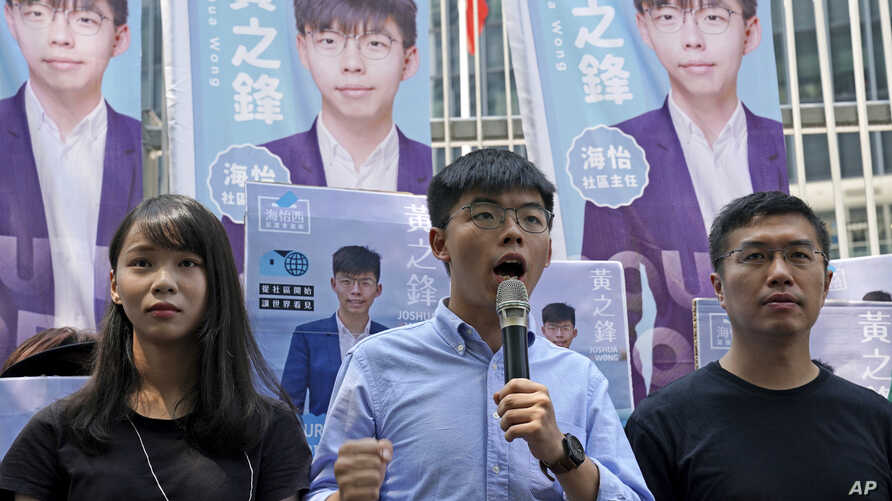 Hong Kong democratic activists, Joshua Wong, center, is accompanied with Agnes Chow, left and pro-democracy lawmaker Au Nok-hin, speaks to the media in Hong Kong, Saturday, Sept. 28, 2019. Wong announced plans to contest local elections and warns…