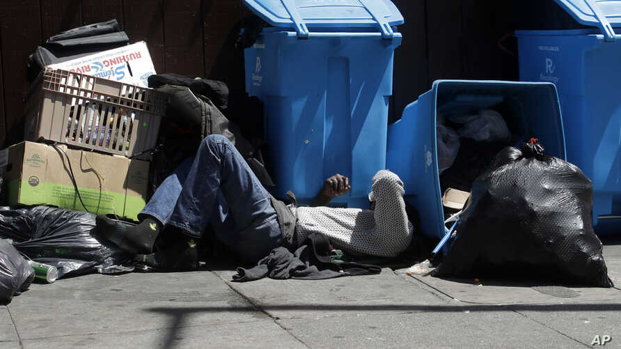 FILE -  In this Aug. 21, 2019, file photo, a homeless man sleeps in front of recycling bins and garbage on a street corner in San Francisco. California Gov. Gavin Newsom is asking President Trump to approve more housing vouchers as Trump's…