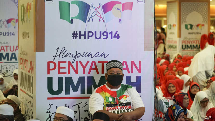 A man sits in front of banners of UMNO (United Malays National Organisation) and PAS (Pan-Malaysian Islamic Party) during an event of officially join alliance in Kuala Lumpur, Malaysia, Saturday, Sept. 14, 2019. Two major opposition parties in…