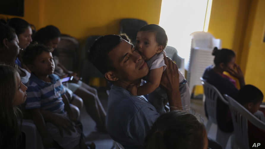 Jose, 31, from Guatemala, holds his 3-month -old daughter during a church service at the Agape World Mission shelter, where many Central American and Mexican migrants stay while trying to reach the U.S. or to request asylum, in Tijuana, Mexico,…