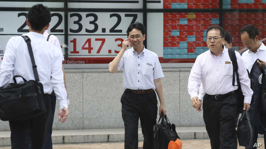 FILE - In this Sept. 6, 2019, file photo, people walk by an electronic stock board of a securities firm in Tokyo. In a report released Wednesday, Sept. 25, 2019, the Asian Development Bank says that escalating trade tensions will sap Asian economies…