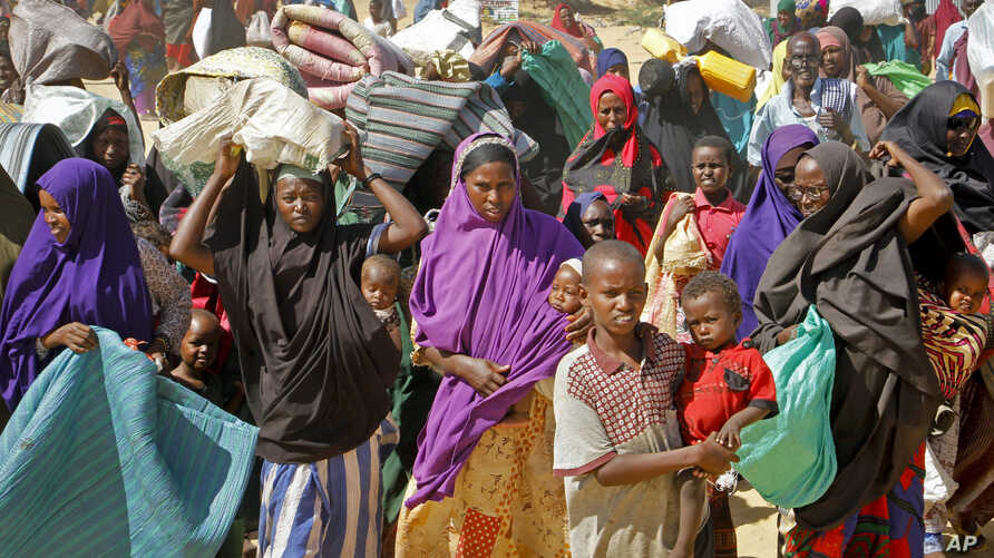 FILE - In this Saturday, May 18, 2019 file photo, people fleeing from drought in the Lower and Middle Shabelle regions of Somalia carry their belongings as they reach a makeshift camp for displaced persons in the Daynile neighborhood on the…