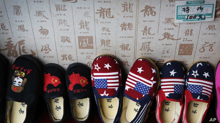 In this July 13, 2018, photo, Chinese made children shoes carrying a Chinese map and U.S. flags are on display for a sale at a shop in Beijing. China announced it filled a World Trade Organization challenge Monday, July 16, 2018,  to U.S. President…