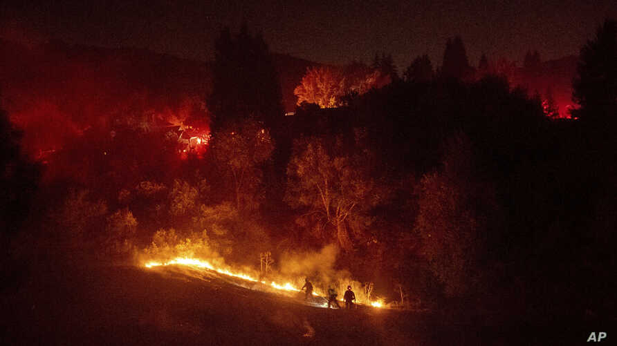 Firefighters work to contain a wildfire burning off Merrill Dr. in Moraga, Calif., on Thursday, Oct. 10, 2019. Police have…