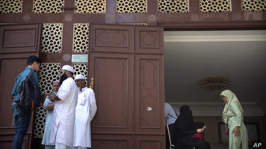 People stand at the entrance to the Kowloon Mosque in Hong Kong