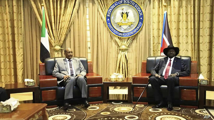 In this photo provided by the official SUNA news agency, Gen. Abdel-Fattah Burhan, left, head of Sudan's sovereign council,…