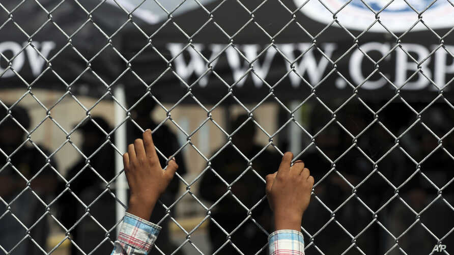 A migrant leans on a fence of the Gateway International Bridge that connects downtown Matamoros, Mexico with Brownsville, Texas…