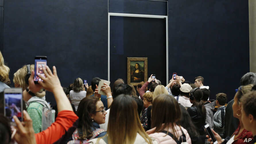 Tourists wait to see Leonardo da Vinci's painting Mona Lisa, at the Louvre museum, in Paris, Wednesday, Oct. 23, 2019. The…