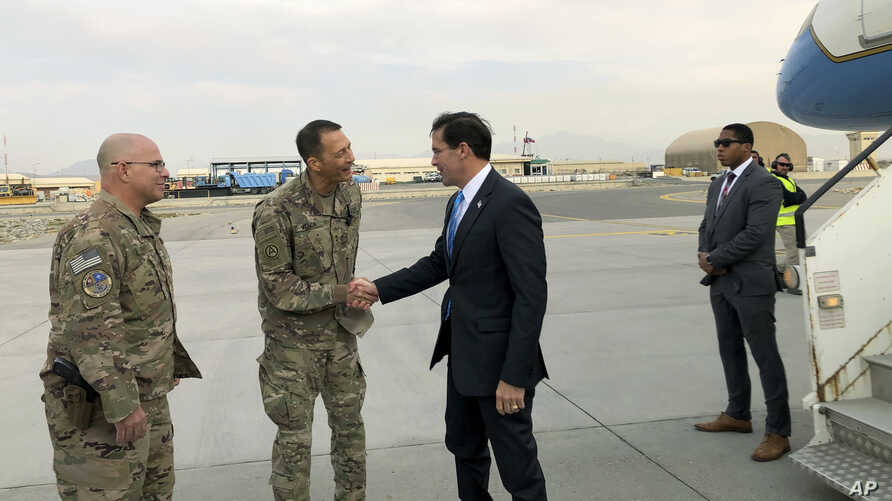 U.S. Defense Secretary Mark Esper, center, is greeted by U.S. military personnel upon arriving in Kabul, Afghanistan, Sunday,…