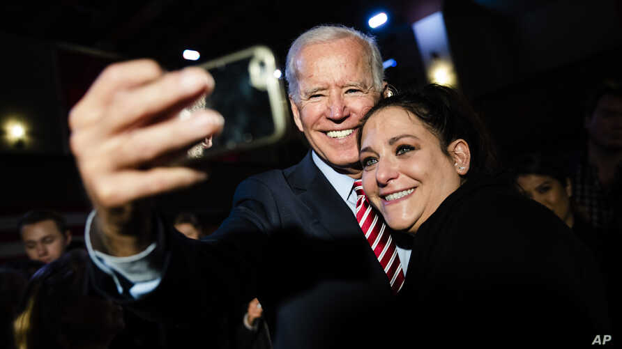 Democratic presidential candidate former Vice President Joe Biden makes a selphie with an attendee during a campaign event,…