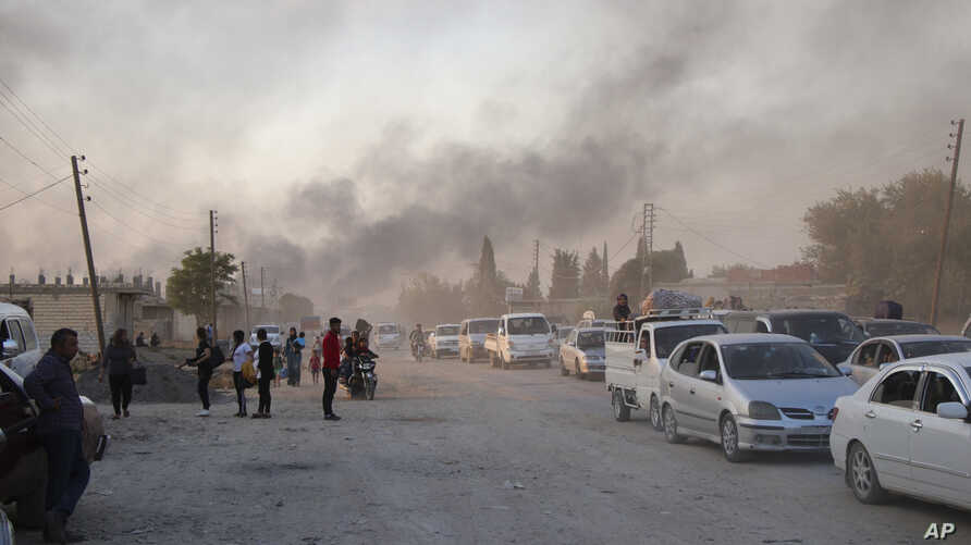 Syrians flee shelling by Turkish forces in Ras al Ayn, northeast Syria, Wednesday, Oct. 9, 2019. Turkish President Recep Tayyip…