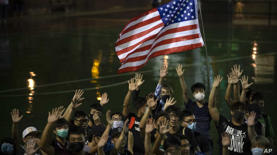 A demonstrator holds a U.S. flag during a rally at the Southorn Playground in Hong Kong, Tuesday, Oct. 15, 2019. Protesters in…