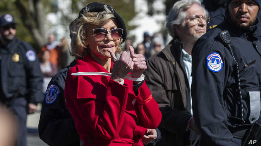 Actress Jane Fonda gestures after being arrested during a rally on Capitol Hill in Washington, Friday, Oct. 18, 2019. A half…