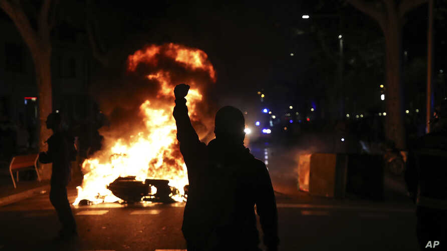 A protestors raises his fist at police across a burning barricade during clashes between protestors and police in Barcelona,…