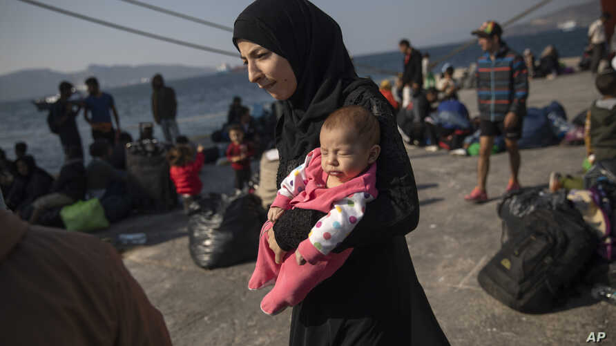 16 year-old Montaha from Aleppo, Syria, walks with her two months daughter Batour after their arrival at the port of Elefsina,…