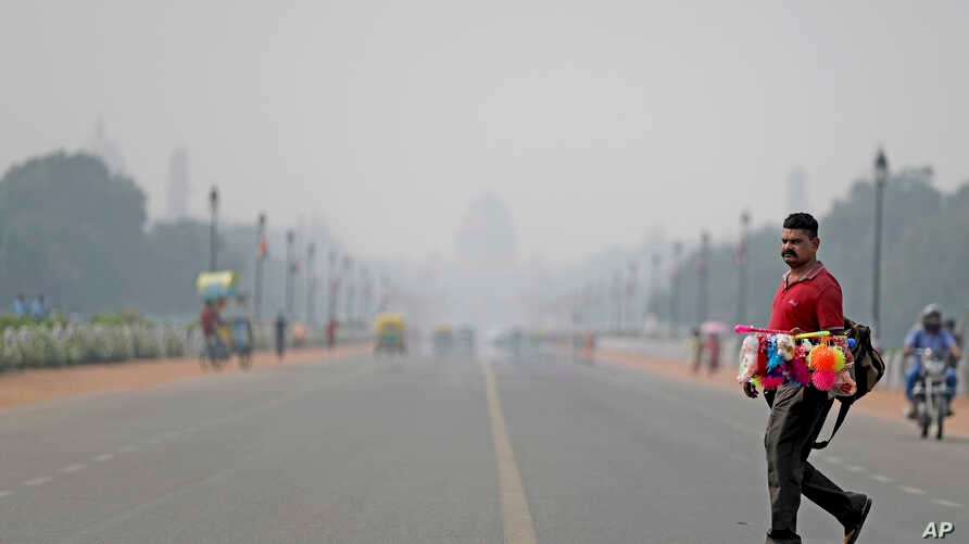 India's Presidential Palace, in the backdrop, is covered with smog as as a roadside vendor crosses Rajapth, the ceremonial…