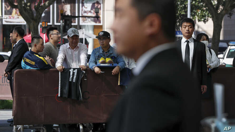 Chinese security officers stand guard as fans carrying jerseys and shoes wait for NBA players to autograph outside the Ritz…
