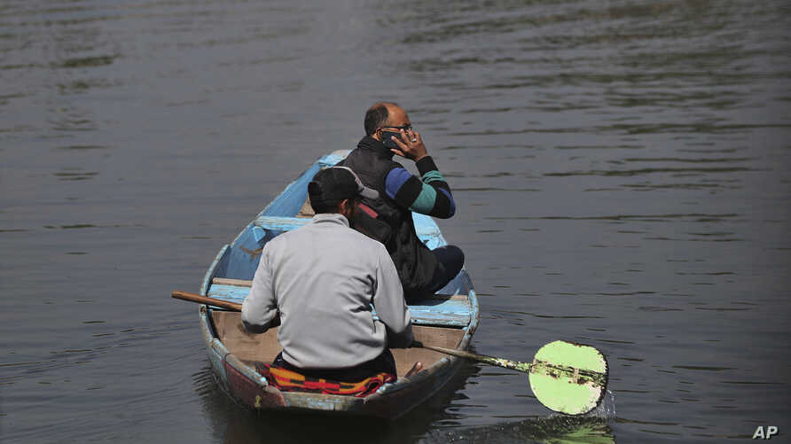 A Kashmiri man talks on his cellphone as he crosses the Dal Lake in Srinagar, Indian controlled Kashmir, Monday, Oct. 14, 2019…