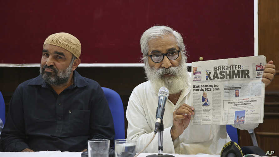 Indian activist and education reformer Sandeep Pandey, right, holds a local daily newspaper of Srinagar, as he addresses a…