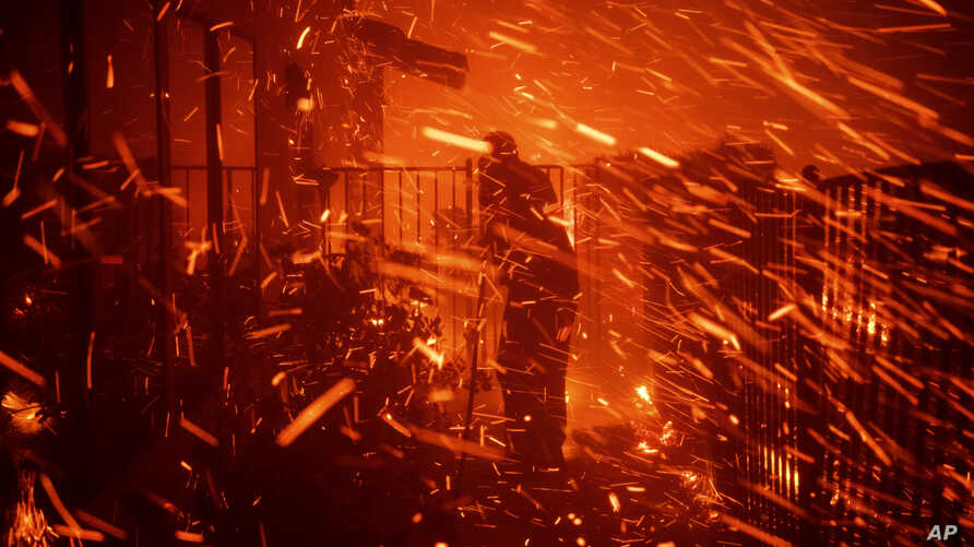 Jerry Rowe uses a garden hose to save his home on Beaufait Avenue from the Saddleridge fire in Granada Hills, Calif., Friday,…