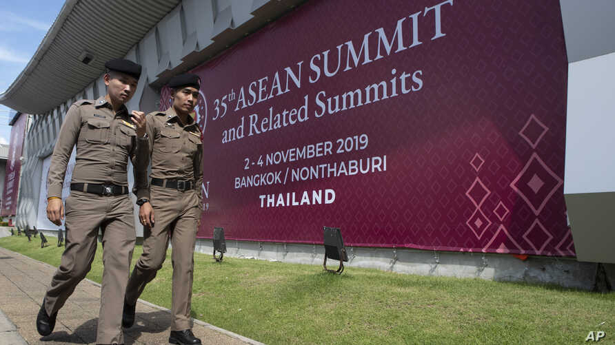 In this Tuesday, Oct. 29, 2019. Thai policemen walk in front of a banner welcoming Association of Southeast Asian Nations at…