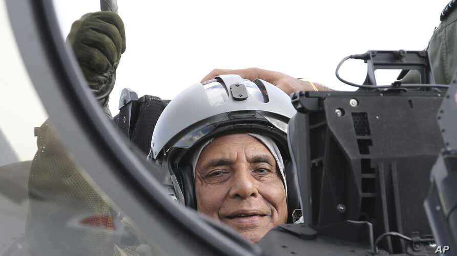 Indian Defense Minister Rajnath Singh thumbs up as he sits in a Rafale jet fighter during an handover ceremony at the Dassault…