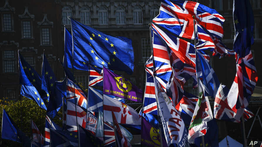 EU and Union flags flap outside the Houses of Parliament in London