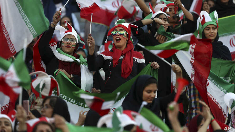 Iranian women cheer during a soccer match between their national team and Cambodia in the 2022 World Cup qualifier at the Azadi…