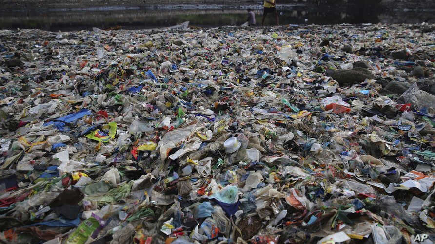 A man walks on the shores the Arabian Sea, littered with plastic and other garbage in Mumbai