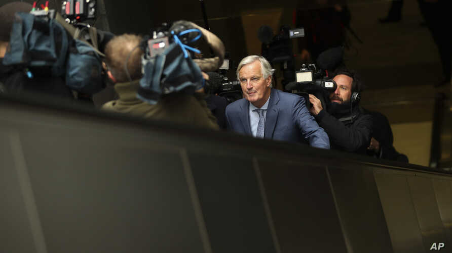 European Union chief Brexit negotiator Michel Barnier, front, rides an escalator surrounded by the media on his way to a…