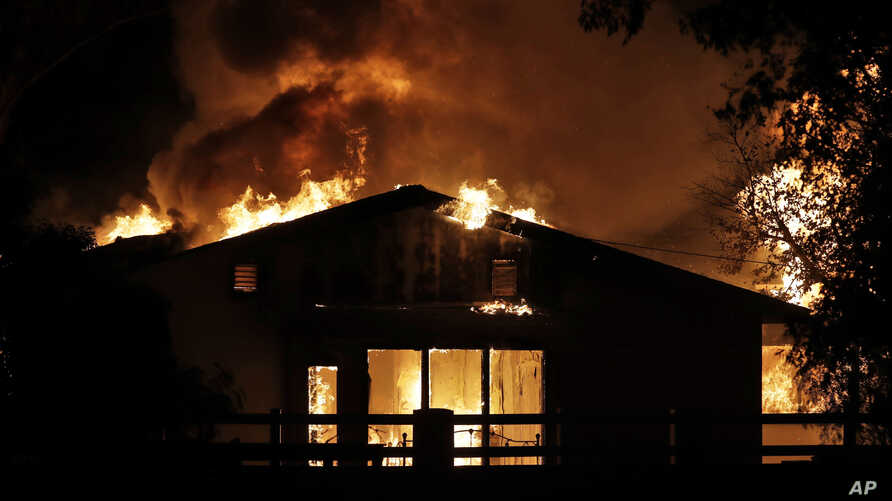 A home goes up in flames in a wildfire zone Thursday, Oct. 24, 2019, in Santa Clarita, Calif. Fast-growing fires across…