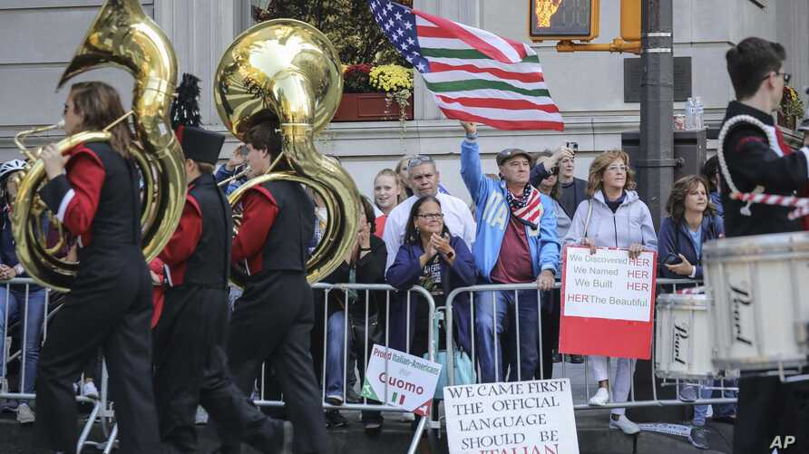 Viewers at the Columbus Day Parade wave a U.S. flag with Italian national colors and signs of expression, Monday Oct. 14, 2019,…