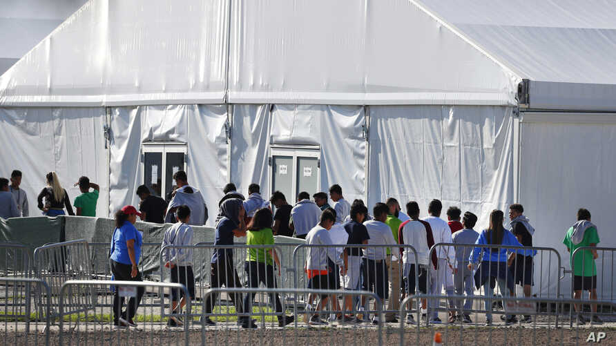 FILE- In this Feb. 19, 2019 file photo, children line up to enter a tent at the Homestead Temporary Shelter for Unaccompanied…