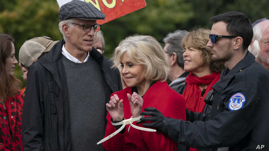Actress and activist Jane Fonda, joined at left by actor Ted Danson, is arrested at the Capitol for blocking the street after…