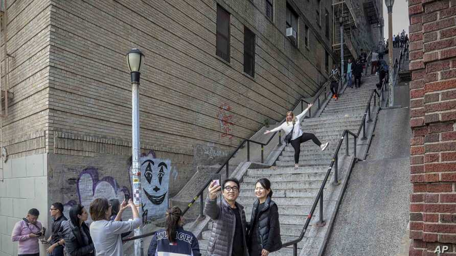 People pose on the steps between two apartment buildings, Monday Oct. 28, 2019, in the Bronx borough of New York. The stairs…