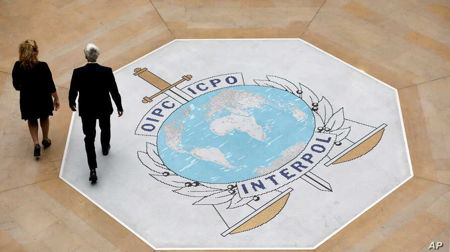 In this photo taken on Thursday, Nov.8, 2018 people walk on the Interpol logo at the international police agency headquarters in Lyon, central France. French authorities say they have closed an investigation into the disappearance and subsequent…