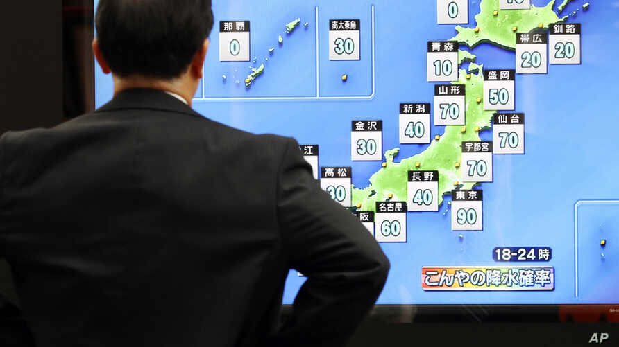 A man watches a public TV of weather forecast in Tokyo Friday, Oct. 11, 2019. Japan's weather agency is warning a powerful…