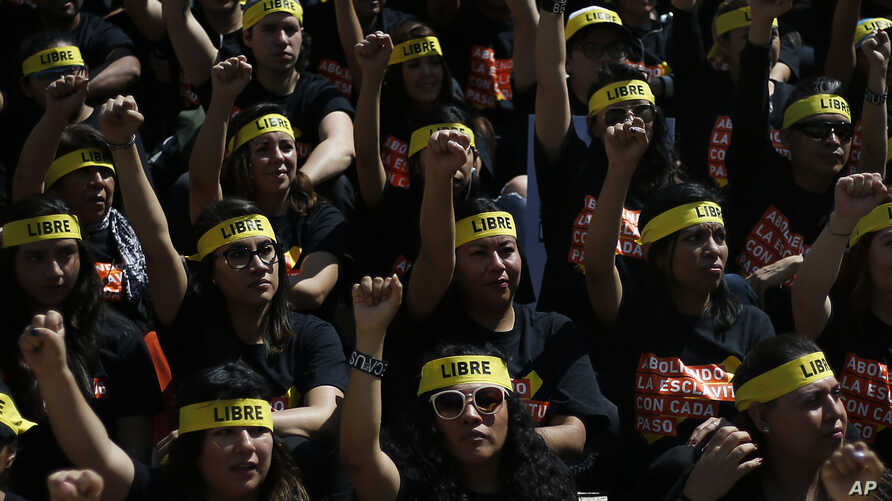 People protesting against human trafficking and slavery raise their fists during a demonstration in Mexico City, Saturday, Oct…