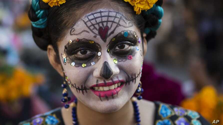Marla Fernandez, 12, poses for a picture before the start of a Day of the Dead parade in Juchitan, Mexico, Wednesday, Oct. 31,…