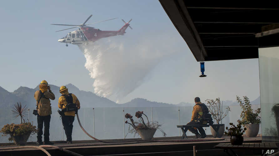 Firefighters watch as a helicopter drops water in a wildfire in the Pacific Palisades area of Los Angeles, Monday, Oct. 21,…