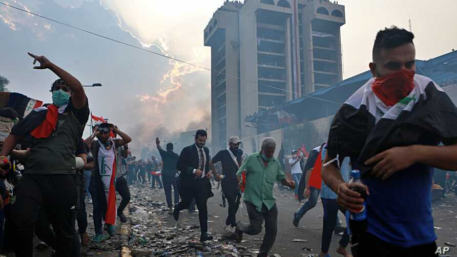 Anti-government protesters run to take cover while Iraqi Security forces fire tear gas during a demonstration in Tahrir Square…