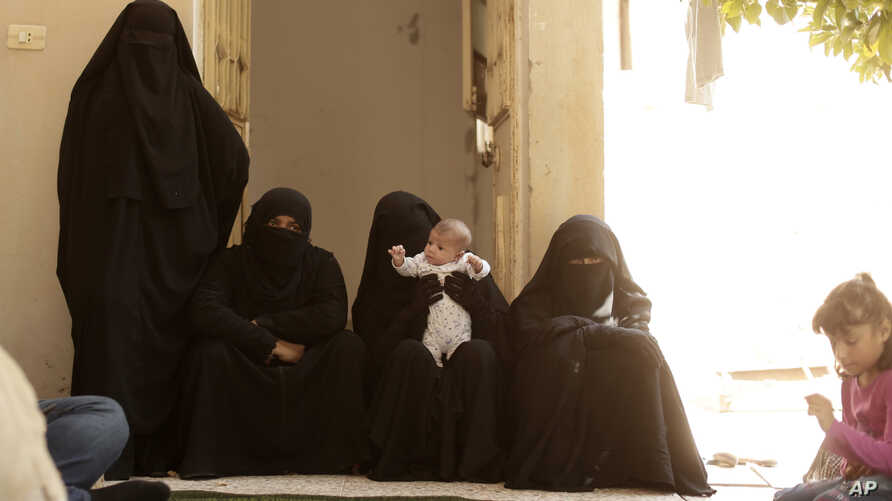 In this Saturday, Sept. 7, 2019, photo, women who recently returned from Al-Hol camp, which holds families of Islamic State members, gather in the courtyard of their home in Raqqa, Syria, during an interview. The Kurdish-led administration has…