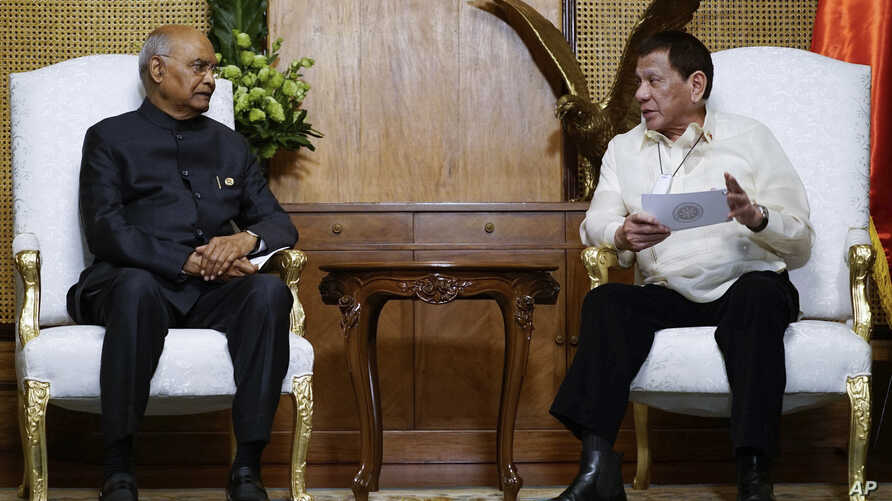 In this photo provided by the Malacanang Presidential Photographers Division, Philippine President Rodrigo Duterte, right,…