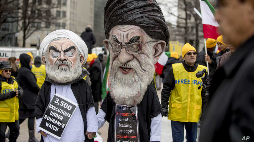 Two people dressed as Iranian President Hassan Rouhani, left, and Iran's supreme Leader Ayatollah Ali Khamenei, right, participate in an Organization of Iranian-American Communities rally in Washington, March 8, 2019.